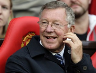 Manchester United's manager Ferguson sits on the bench during pre-season friendly soccer match in Manchester